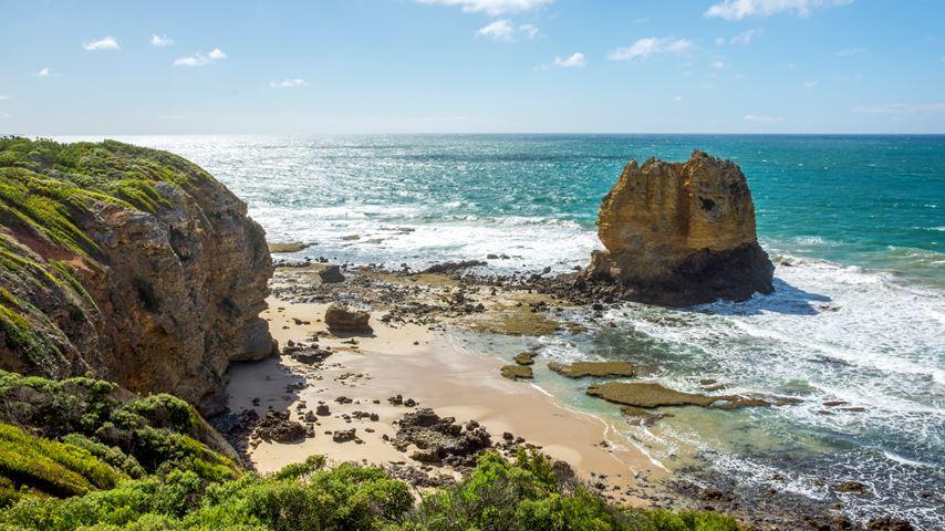Bovenaanzicht op een stuk strand in Australië. In de blauwe zee ligt Eagle Rock, een bekende grote rots. De lucht is blauw.