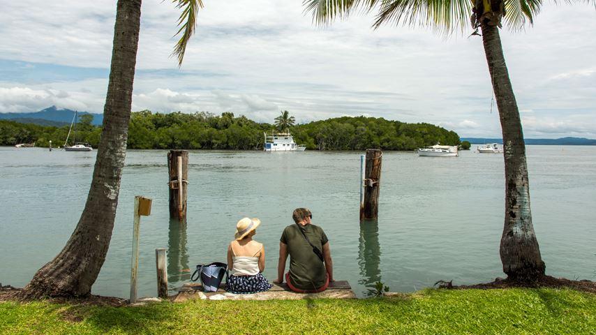 Een man en vrouw, op de rug gezien, zitten onder een palmboom en kijken naar het water en bootjes bij Port Douglas in Australië.