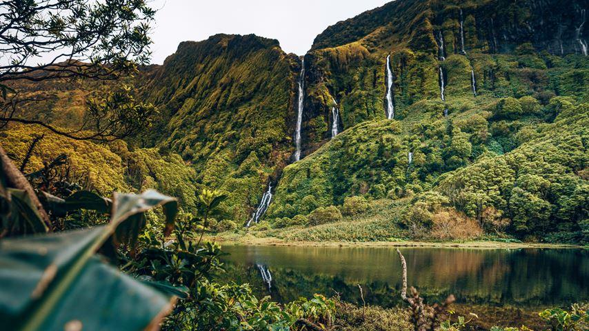 Een rotswand met meerdere watervallen op het Azoorse eiland Flores. Op de voorgrond een spiegelend meer.