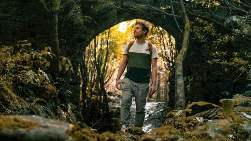 Een man loopt onder een oude stenen brug in een donker bos op het Azoorse eiland São Miguel.