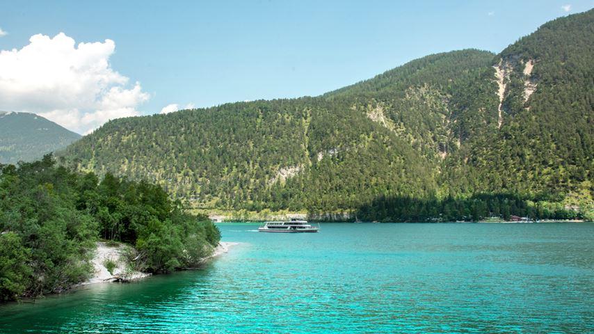 Een boot vaart op de blauwe Achensee in Oostenrijk. Op de achtergrond zijn een begroeide heuvel en een blauwe lucht te zien.
