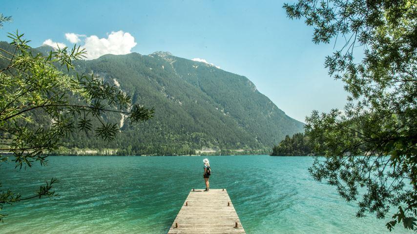 Een vrouw kijkt uit op de Achensee in Oostenrijk. Het meer is groenblauw. Op de achtergrond is een berg te zien.