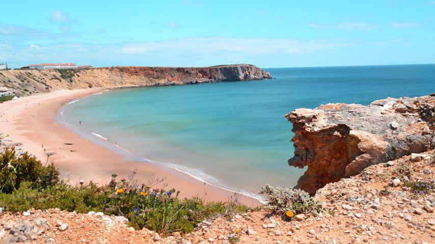 Een baai van het Portugese strand Praia de Mareta. De zee is blauw. Op de voorgrond ligt een grote rots.