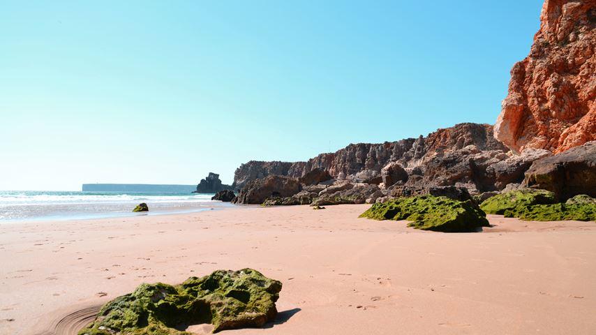 Rotspartijen en het Portugese strand Praia do Tonel. De lucht is blauw. Enkele rotsen zijn begroeid met mos.