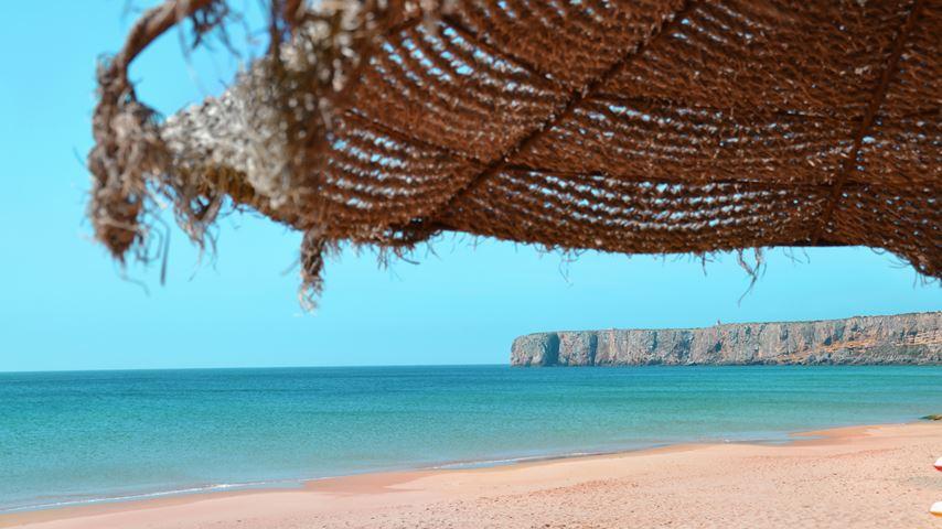 Uitzicht op het Portugese strand Praia de Mareta met een blauwe zee erachter. Een grote parasol op de voorgrond.