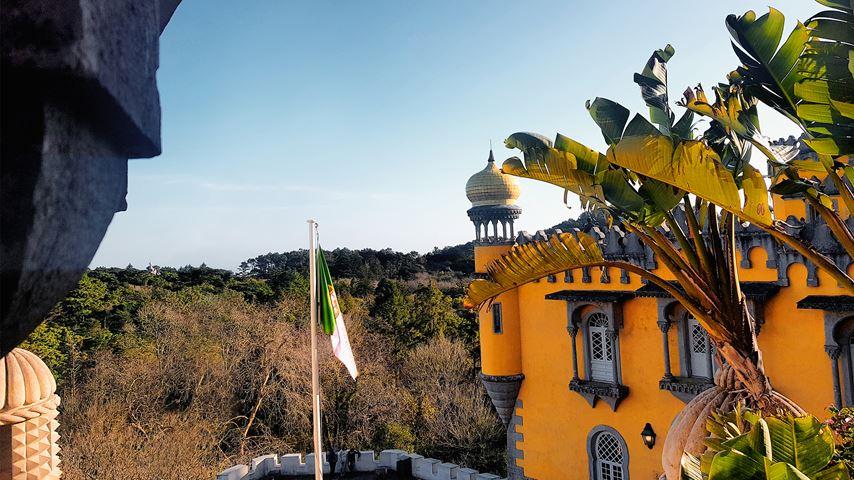 Palácio da Pena in Portugal. Op de voorgrond een stuk van het gele paleis en bladeren. Op de achtergrond een toren.