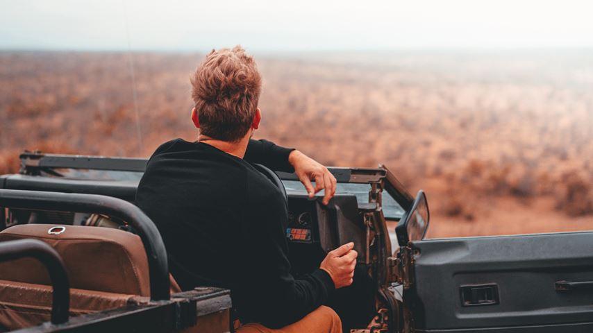 Krugerpark, Zuid-Afrika. Een man, op de rug gezien, zit in een jeep en kijkt naar een vlak landschap. De omgeving is onscherp.