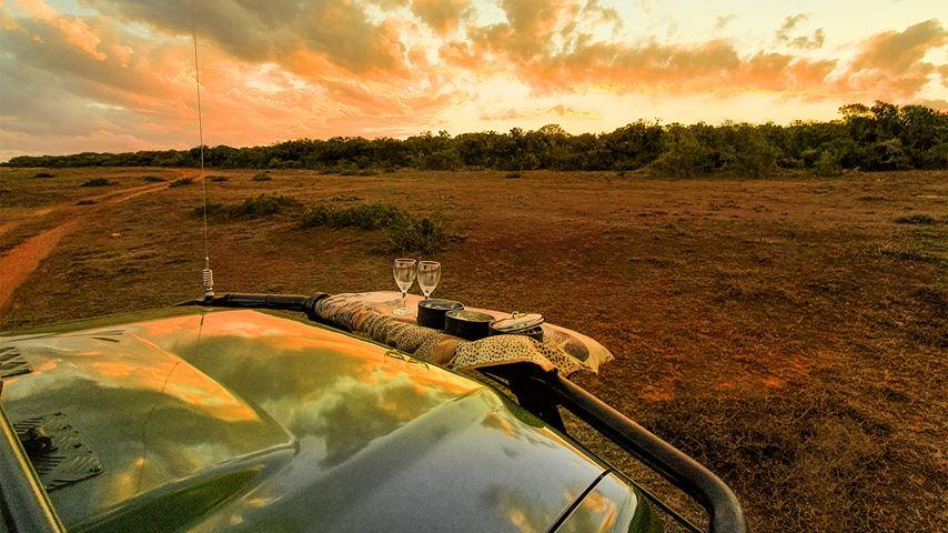 Zonsondergang in Shamwari, Zuid-Afrika. Een jeep staat op de voorgrond. Op de achtergrond rood-oranje wolken.