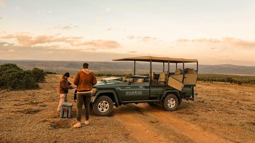 Shamwari, Zuid-Afrika. Twee mannen staan bij een safari jeep. Op de achtergrond rood-oranje wolken.