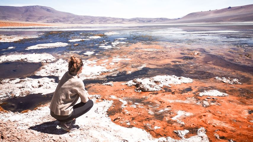 In het Reserva Nacional Los Flamencos in Chili zit een vrouw gehurkt te kijken naar roestkleurige water.