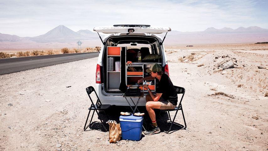 Een man, in de Atacama woestijn in Chili, zit achter de camper te eten.