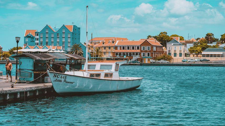 Een boot in het blauwe water van Curaçao. Op de achtergrond is een deel van Willemstad te zien.