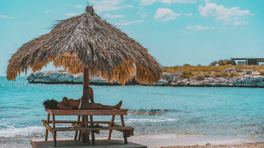 Een man ligt op het strand van Curaçao onder een rieten parasol naar de blauw-groene zee te kijken.