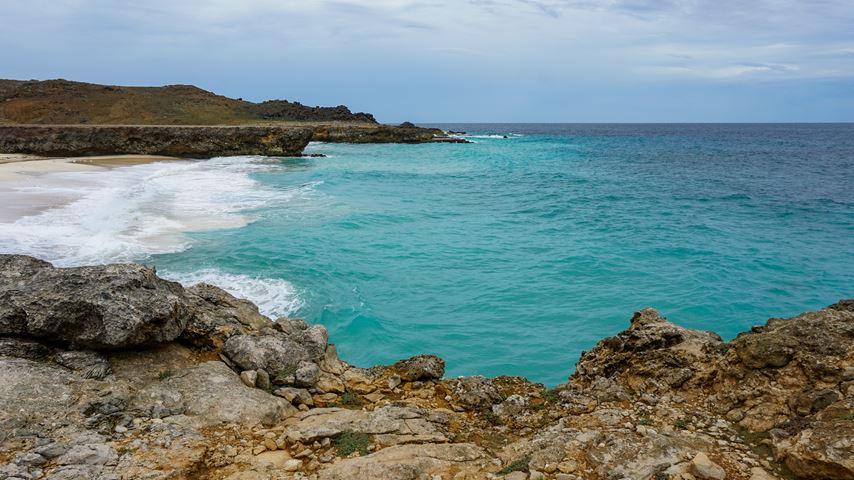 Dos Playa Beach op Aruba. Vanaf rotsen uitzicht op een klein strand en blauwe zee.
