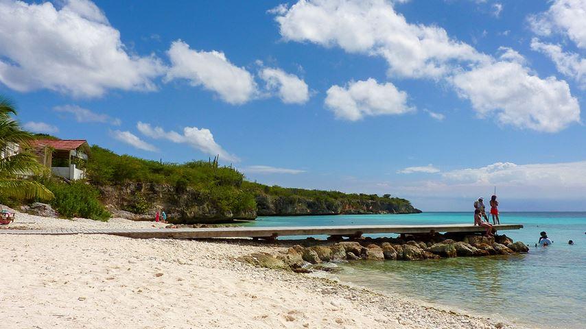 Strand op Curaçao. Mensen staan te vissen op een steiger. De zee is groen-blauw en de lucht is blauw maar bewolkt.
