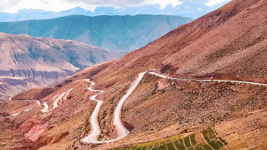 Uitzicht van bovenaf op een busje die rijdt op een kronkelweg in Argentinië. Roodgekleurde bergen en een wolkendek er omheen.
