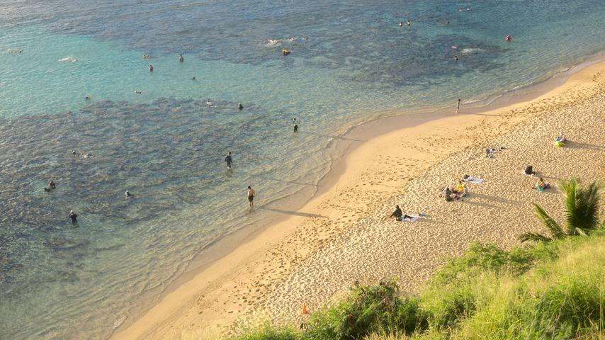 Hanauma Bay op Hawaii gezien van bovenaf. Een geel strand en blauwe zee met een klein aantal mensen.