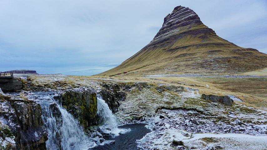 De berg Kirkjufell op Ijsland. De berg ziet eruit als een punthoed. Op de voorgrond zijn kleine watervallen en sneeuw te zien.