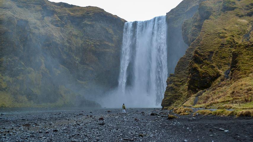 De 60 meter hoge en 25 meter brede waterval Skógafoss in het zuiden van IJsland. Voor de waterval staat een vrouw