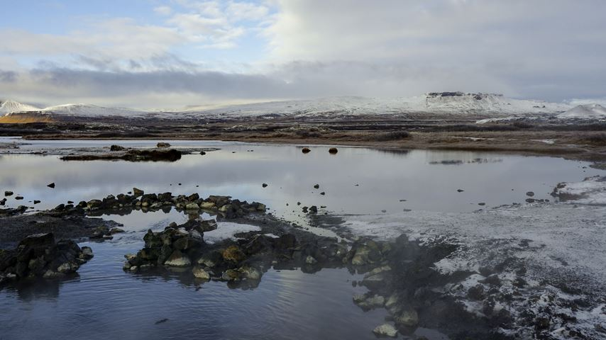 Weids uitzicht op de Ijslandse warmwaterbronnen van Landbrotalaug. Kalme wateren. De lucht is blauw met wolken.