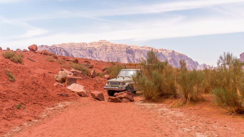 In de Jordanese Wadi Rum woestijn staat een jeep stil voor een paar grote rode keien op de weg.