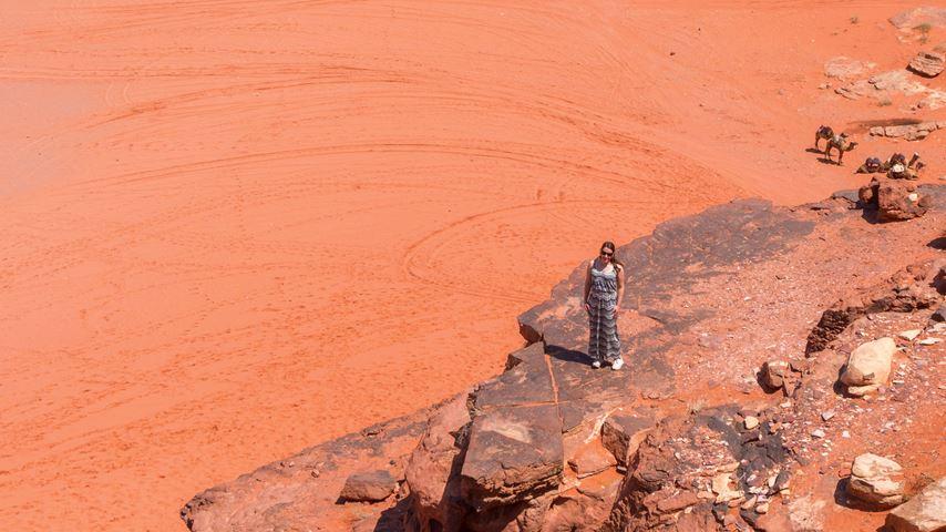Een vrouw, van bovenaf gezien, staat op de Red Sand Dune in de Jordanese Wadi Rum woestijn. Zandsteen, rotsen en rood zand vormen het decor